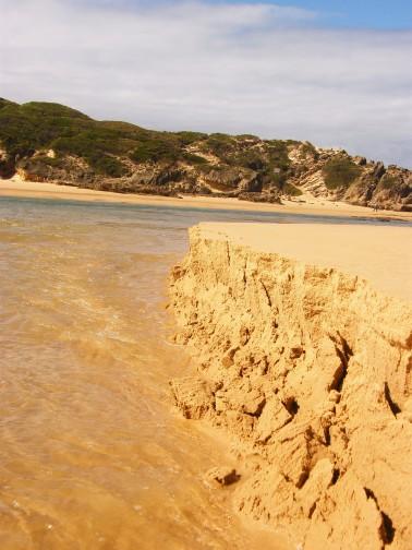 Tide crumbling the sandbank